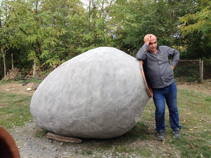 Our driver Beso takes a break next to a full-size kvevri in Kakheti.